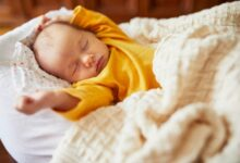 Newborn-baby-sleeping-under-knitted-blanket-cm