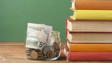 Jar stufffed with $50 bills on desk by schoolbooks