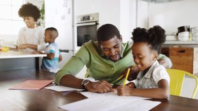 African-American-father-homeschooling-daughter-at-kitchen-table