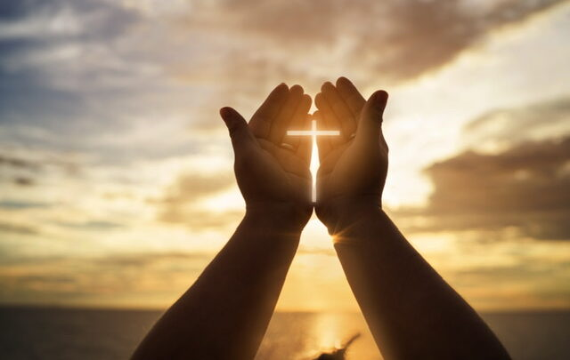 Hands cupped around the sunrise with a cross shining through