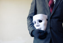 Man in a Suit With a Mask by His SIde