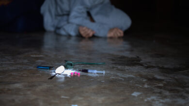 Addict with a syringe using drugs on the floor.