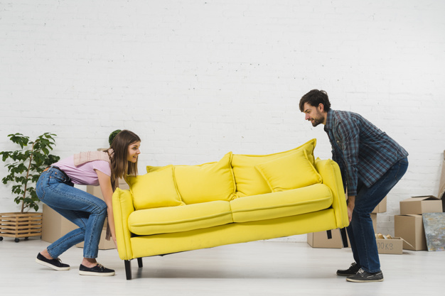 happy-young-couple-placing-yellow-sofa-living-room_23-2148095448