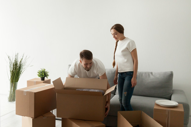 young-spouses-carrying-boxes-relocating-new-flat_1163-4144