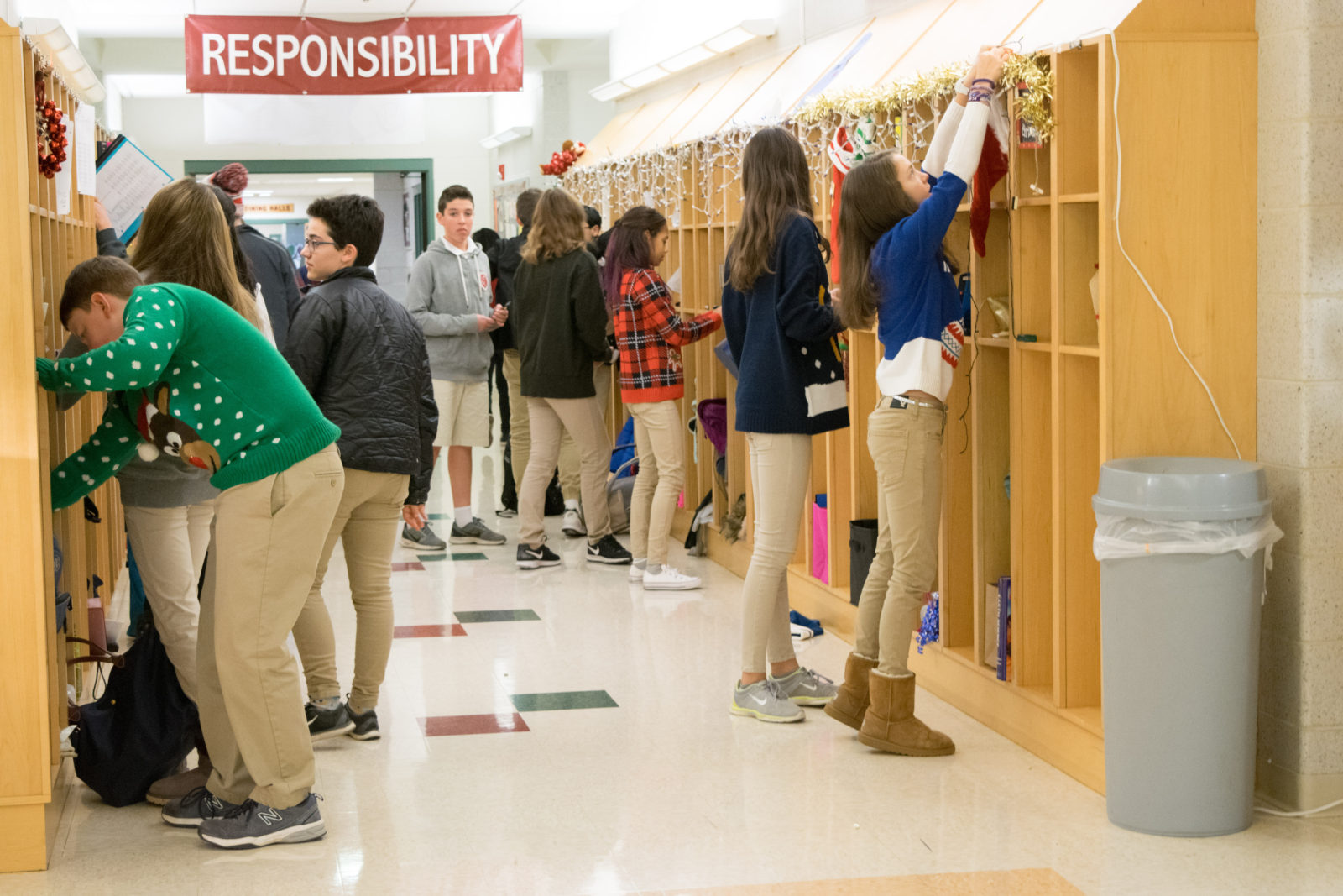 Students prepare for their day while hanging holiday decorations on their lockers.