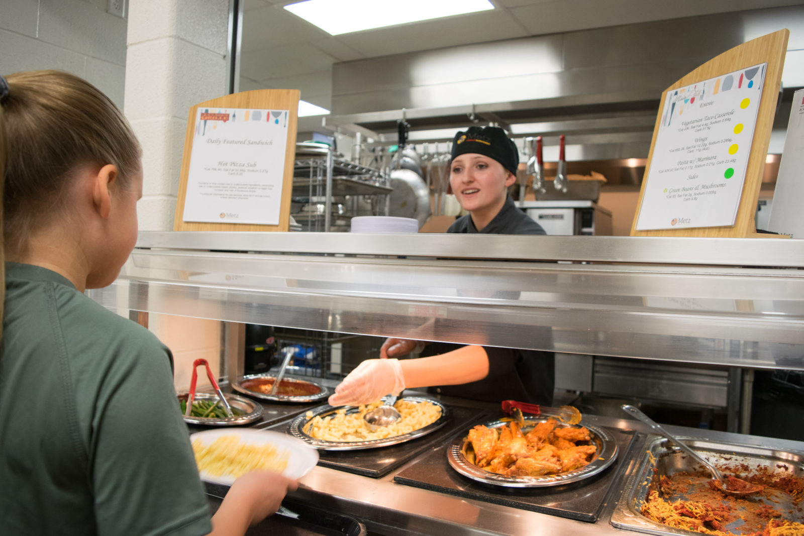 Students receive their lunch at the warm plate section.