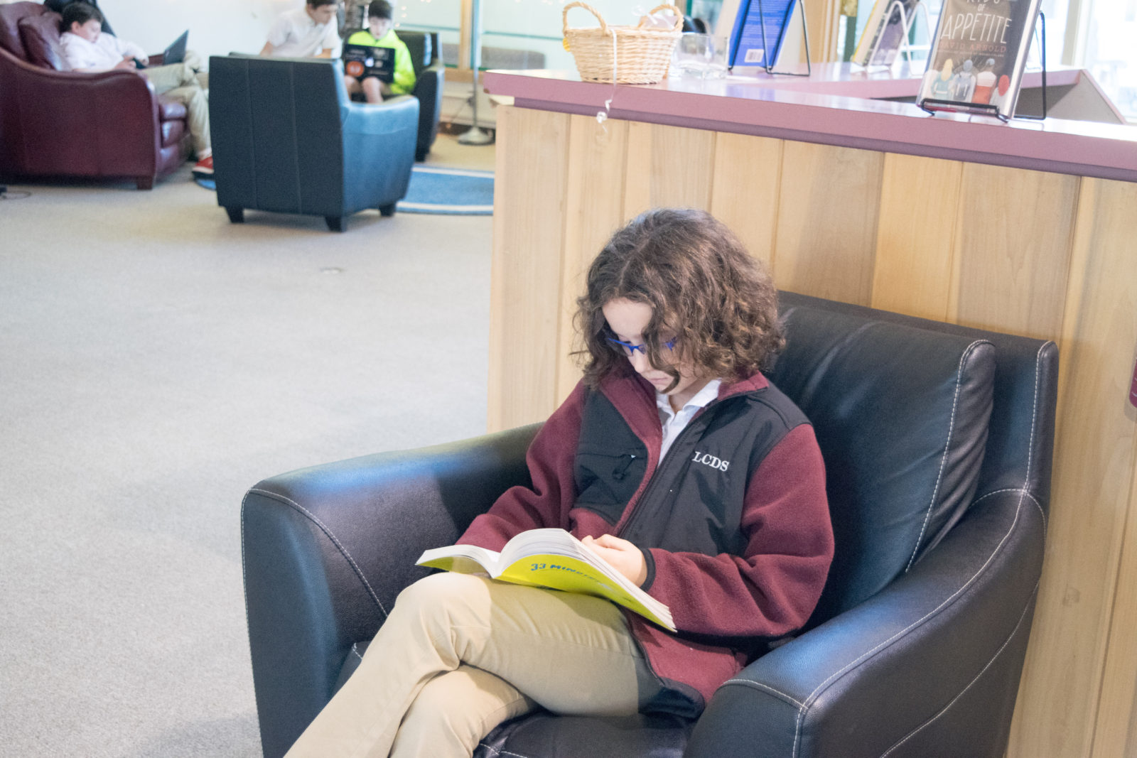 A student reads in the library before school starts.
