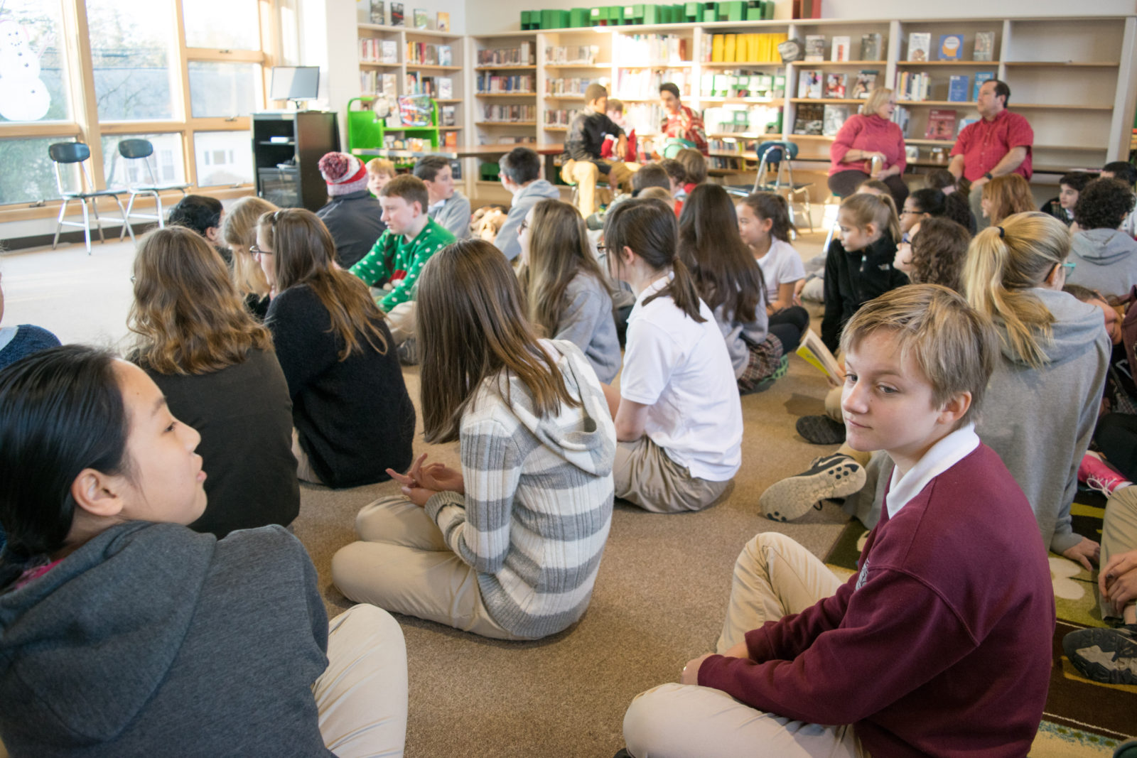 The Middle School is sitting and talking in the library before morning meeting starts.