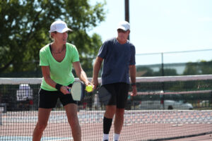 Woman and man playing a fierce game of pickleball