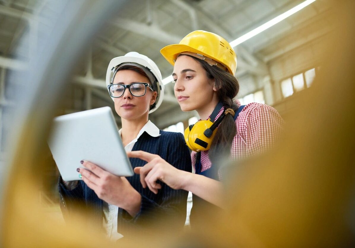 Two women reviewing plans at a job site while wearing protective equipment