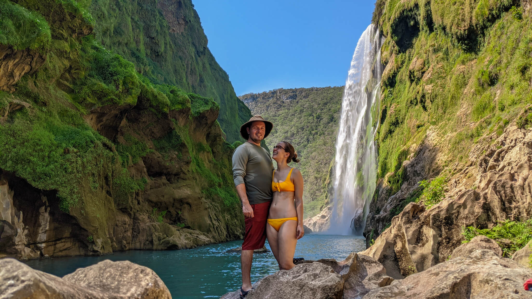 Couple smiling in front of Tamul waterfall and Tampaon river in Ciudad Valles, Huastecas, Mexico.