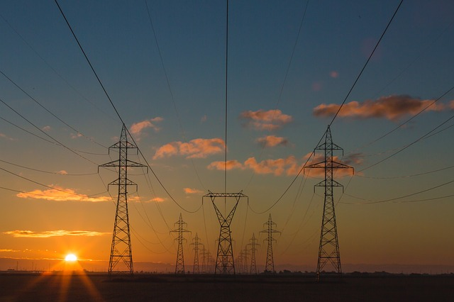 Photo of main power lines with a setting sun. This is used to illustrate commercial rates page.