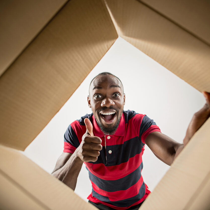 The surprised afrocan man unpacking, opening carton box and looking inside. The package, delivery, surprise, gift lifestyle concept. Human emotions and facial expressions concepts