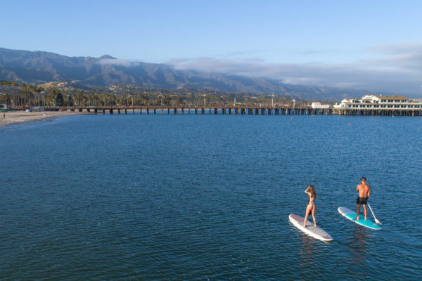 Photo of several people on paddle boards at the beach