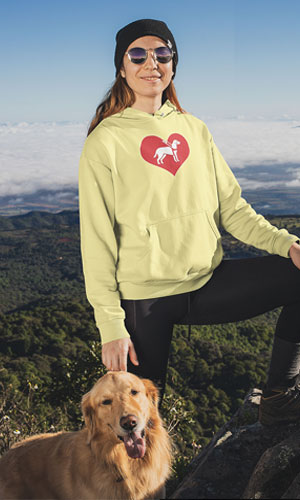 A woman wearing a yellow sweatshirt with the I love guide dogs symbol