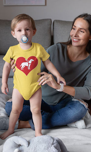 A baby in a yellow jumper with the I love guide dogs symbol