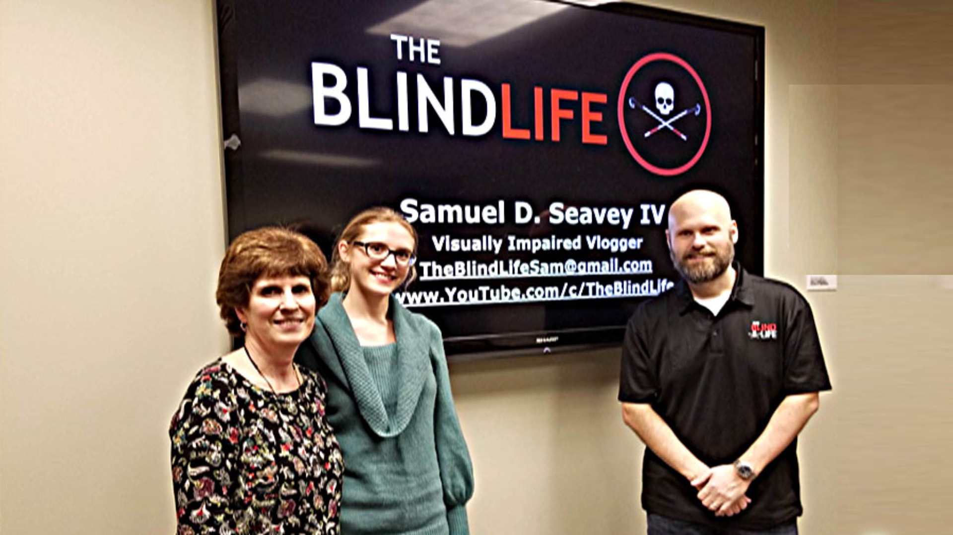 Sam Seavey in front of The Blind Life Poster  at a Speaking Engagement