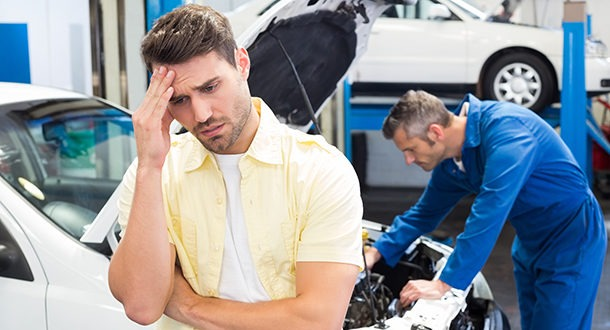 Worried customer with mechanic looking at car