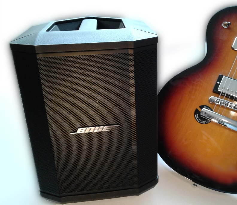The Bose S1 Pro, set next to a Gibson Les Paul for a size comparison.