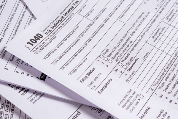 A variety of United States tax forms with a pencil