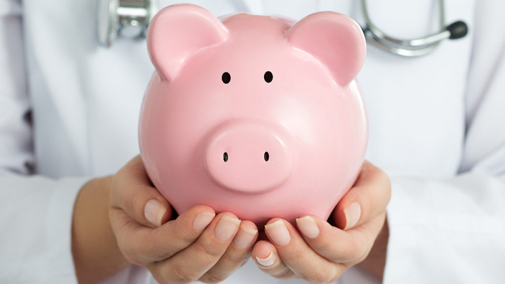 Female Doctor Holding Piggy Bank. Doctor's hands close-up. Medical insurance and health care concept.