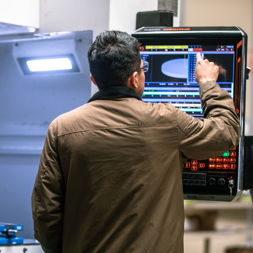 Cencal CNC employee working on CNC Machine in the Central Valley