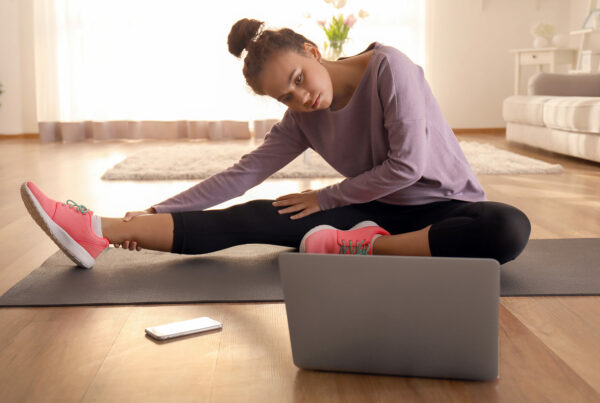 Young woman stretches her leg in front of a computer screen