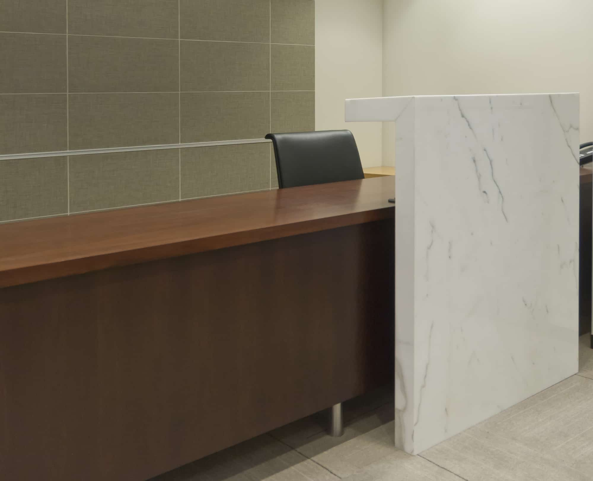 corporate interiors reception desk with wood and carera marble