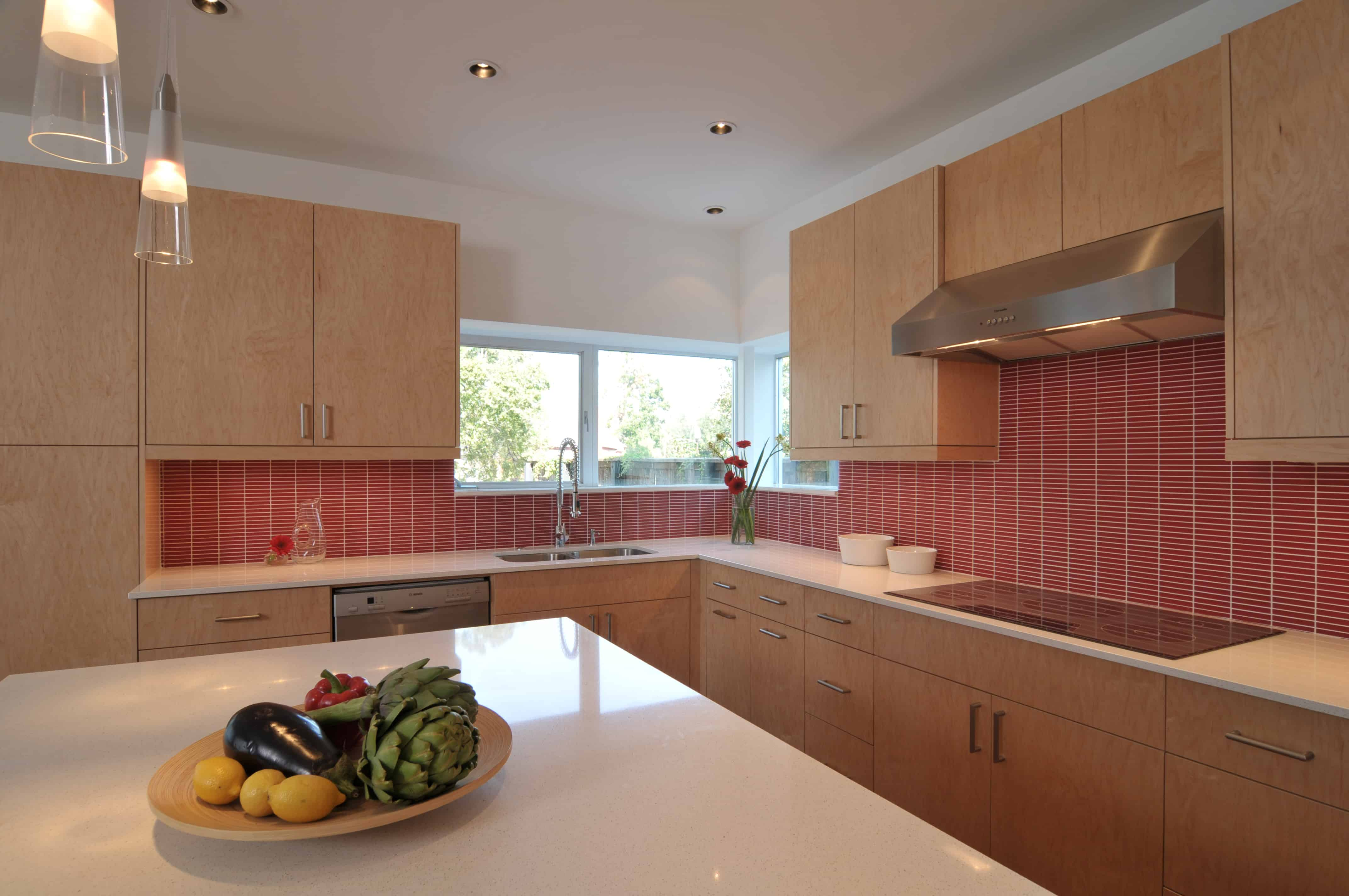 Southmore terrace sustainable houston modern home kitchen accented by vibrant red glass tile.