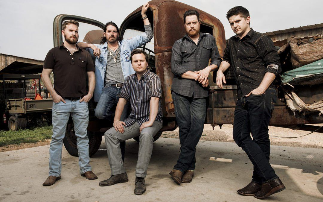 group of five men posed in front of old pick up truck