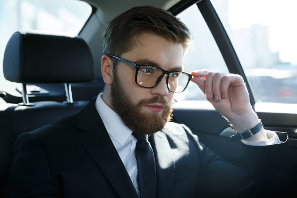Portrait of a serious young man wearing suit and eyeglasses while sitting in car