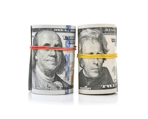 Two rolls of US Currency with rubber bands around the presidents eyes.