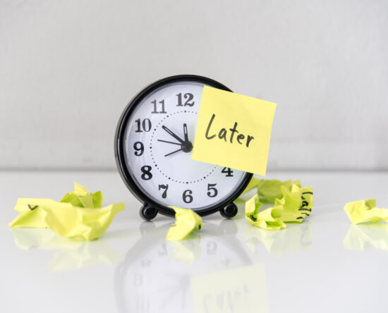 """Picture of clock with """"later"""" sign over it"""