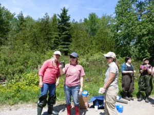 Adrienne Kohl, Nancy Fyfe and Lisa Neville stand along the banks of the Talbot River holding up the Nitrate testing equipment looking at their results