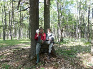 """Ted Greatrix and Ingrid VanderMarel sitting on a natural """"tree bench"""" in Copeland Forest with their boots in the air.  Ted is clutching his kitchen sieve"""