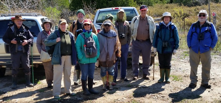 group of people in outdoor clothing standing in a parking lot