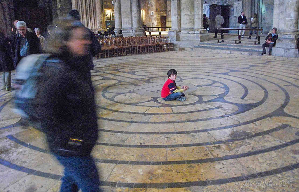Boy sits in the middle of the Chartres Labyrinth by Jill K H Geoffrion
