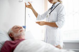 A Nurse Hangs an Iv Bag for a man in the hospital
