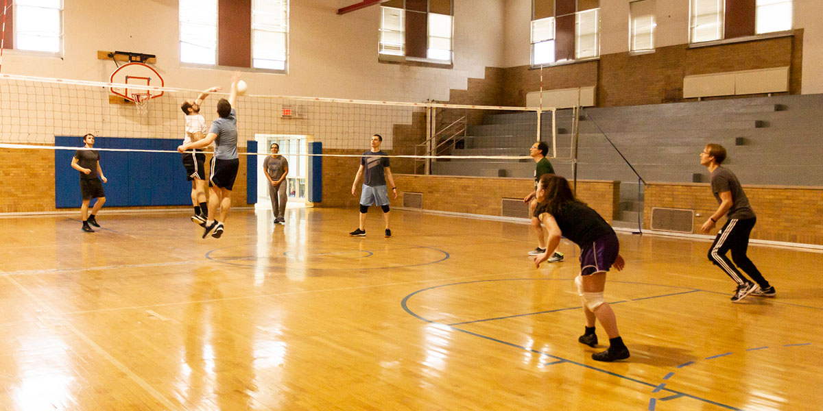 Engineers playing volleyball in the QSAI gym