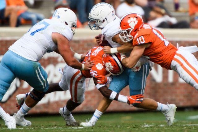 The Citadel freshman Cooper Wallace (27) is tackled by Clemson linebacker Baylon Spector (10) and cornerback Sheridan Jones (26) during the first quarter of their game against The Citadel Saturday, Sept. 19, 2020.