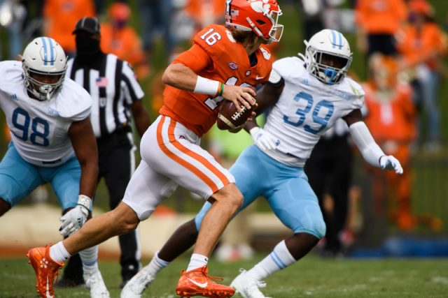 Clemson quarterback Trevor Lawrence (16) attempts to evade The Citadel linebacker Anthony Britton Jr. (39) and defensive lineman ay Smith (98) during their game Saturday, Sept. 19, 2020.