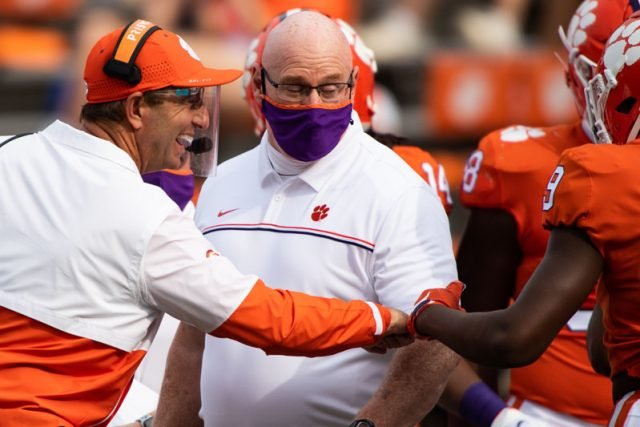 Clemson head coach Dabo Swinney celebrates with Clemson running back Travis Etienne (9) during the second quarter of their game Saturday, Sept. 19, 2020.