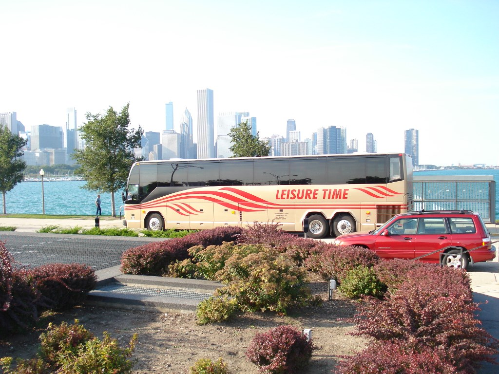 Bus parked by river in front of city skyline