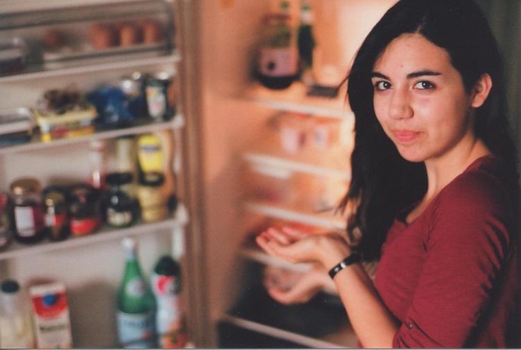 woman standing by an open fridge