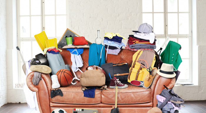 A couch in a room that is full of clutter of junk