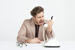 Agitated man screaming into the phone.