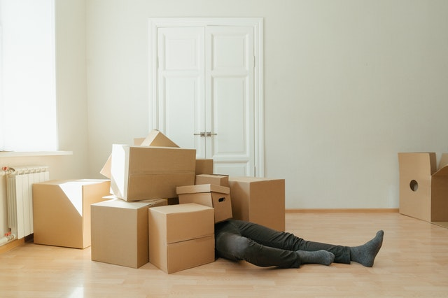 Person in dark jeans covered with boxes