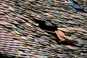 Roof of a house with damaged tiles.
