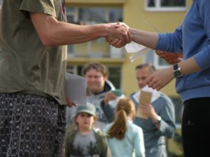 People shaking hands in front of a house.