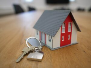 A set of keys next to a miniature wooden house.